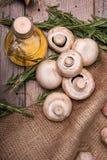 Состав свежих грибов, бутылки масла и розмаринового масла на деревянной предпосылке Естественный и целительный образ жизни Стоковое фото RF