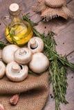 Состав свежих грибов, бутылки масла и розмаринового масла на деревянной предпосылке Естественный и целительный образ жизни Стоковое Фото