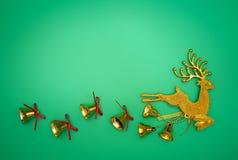 Состав северного оленя золота рождества Подарок рождества, северный олень золота и колокол на зеленой предпосылке Плоское положен стоковое фото rf