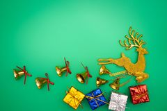 Состав северного оленя золота рождества Подарок рождества, северный олень золота и колокол на зеленой предпосылке Плоское положен стоковые фотографии rf
