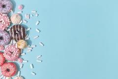 Состав сладких застекленных donuts и помадок на голубой предпосылке Взгляд сверху Концепция children' праздник s Космос для  стоковые изображения rf