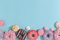 Состав сладких застекленных donuts и помадок на голубой предпосылке Взгляд сверху Концепция children' праздник s Космос для  стоковое изображение