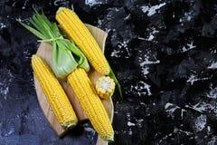 Состав сладостной сырцовой мозоли на ударах с листьями Рецепт еды на темной предпосылке Овощи Плоское положение скопируйте космос стоковые изображения