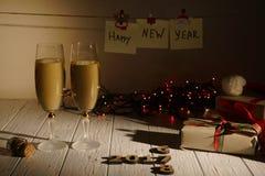 Состав 2 стекел шампанского, обернутых подарков, накаляя гирлянд и деревянных номеров показывая год на Стоковые Фото