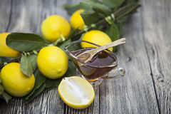 Состав стеклянной вазы с флористическим медом и деревянной ложкой с лимоном на деревянной предпосылке Стоковая Фотография