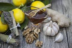 Состав стеклянной вазы с флористическим медом и деревянной ложкой с грецкими орехами, чесноком и имбирем трав лимона провансальск Стоковая Фотография RF