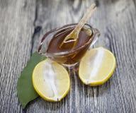 Состав стеклянной вазы с флористическим медом и деревянной ложкой с лимоном на деревянной предпосылке Стоковое Фото