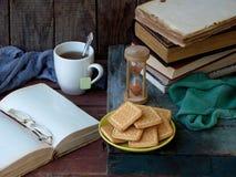 Состав стога старых книг, открытой книги, чашек чая, стекел и плит печений сахара на деревянной предпосылке Винтаж Стоковые Изображения RF