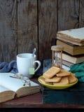 Состав стога старых книг, открытой книги, чашек чая, стекел и плит печений сахара на деревянной предпосылке Винтаж Стоковое фото RF