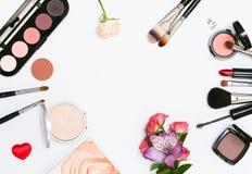 Состав с косметиками, щетками, shadoes и цветками состава на белой предпосылке Стоковые Фотографии RF
