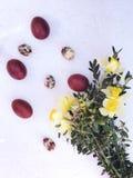 Состав с покрашенными яйцами цыпленка и триперсток в гнезде и цветках стоковые фотографии rf
