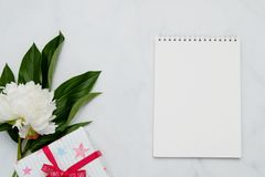 Состав с цветками и тетрадью на белой предпосылке Насмешка вверх для вашего дизайна Плоское положение стоковое изображение rf
