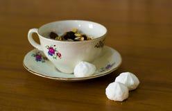 Состав чашки и поддонника фарфора заполнил с югуртом и muesli и 3 белыми помадками Стоковые Изображения