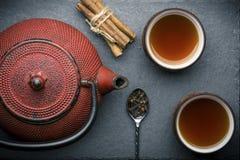 Состав чая с керамическими чашками чая и чайником красного цвета железным на темной каменной предпосылке Стоковое Изображение