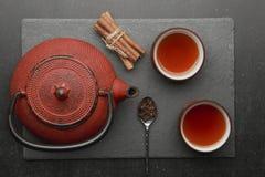 Состав чая с керамическими чашками чая и чайником красного цвета железным на темной каменной предпосылке Стоковые Фото