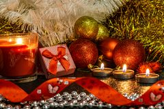 Состав ` s рождества и Нового Года красных шариков для рождественских елок и золотой сусали, в свете свечей на темном backgro стоковое фото