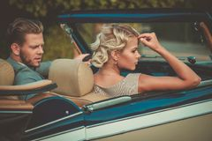 Состоятельные молодые пары в классическом автомобиле с откидным верхом Стоковые Изображения RF