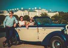Состоятельные друзья приближают к классическому автомобилю с откидным верхом стоковое изображение