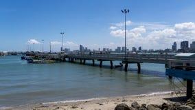 Состыкуйте на пляже с городом в предпосылке Стоковые Изображения