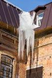 Сосульки висят от крыши здания Зима или день весны солнечный Стоковые Изображения