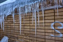 Сосульки висят от крыши старой стены, последней зимы или предыдущей весны стоковая фотография rf