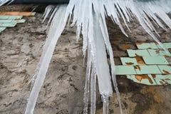 Сосульки вися от крыши старого кирпичного здания с кубами старых плиток, травматичного горькосоленого льда, таяния в предыдущей в Стоковое Изображение RF