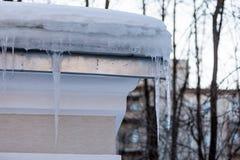 Сосульки под крышкой снега на крыше здания в марте на заходе солнца Стоковое Изображение