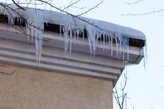 Сосульки под крышкой снега на крыше здания в марте Стоковое Фото