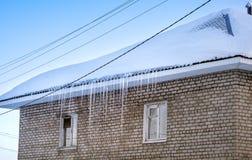 Сосульки вися от крыши кирпичного здания Тop bui Стоковое Изображение