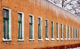 Сосульки вися от крыши старого кирпичного здания Стоковая Фотография