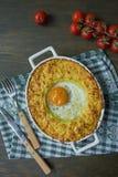 Сотейник картошки с bolognese Сотейник печеного картофеля с яйцом и заскрежетанным сыром в керамическом овальном печь листе Дерев стоковое фото rf