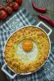 Сотейник картошки с bolognese Сотейник печеного картофеля с яйцом и заскрежетанным сыром в керамическом овальном печь листе Дерев стоковое изображение rf