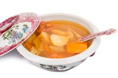 Сотейник китайских картошек, морковей и супа томатов изолированного в белизне Стоковая Фотография
