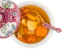Сотейник китайских картошек, морковей и супа томатов изолированного в белизне Стоковое фото RF