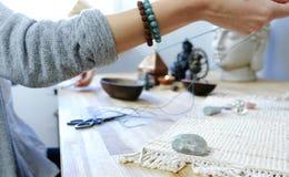 Соткать шариков Конец-вверх ` s женщины вручает шнуровать шарики на потоке, делая ювелирные изделия в мастерской Стоковое фото RF