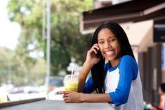 Сотовый телефон счастливой молодой чернокожей женщины говоря на кафе outdoors Стоковое Изображение RF