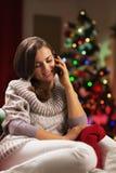 Сотовый телефон молодой женщины говоря около рождественской елки Стоковая Фотография