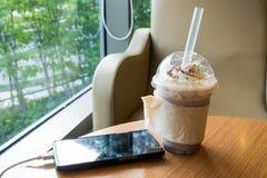 Сотовый телефон поручая в кафе с пластичной чашкой замороженного frappe шоколада стоковое фото rf