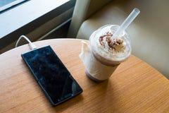 Сотовый телефон поручая в кафе с пластичной чашкой замороженного frappe шоколада стоковое изображение rf