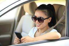 сотовый телефон пользы водителя женщины в автомобиле Стоковая Фотография