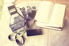 Сотовый телефон, старая камера и книги на деревянном столе Стоковое фото RF