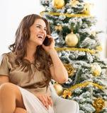 Сотовый телефон счастливой женщины говоря пока сидящ около рождественской елки Стоковые Фотографии RF