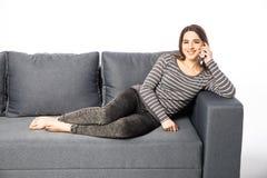 Сотовый телефон счастливой молодой женщины говоря пока лежащ на софе на белизне Стоковое Фото