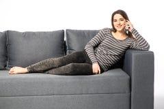 Сотовый телефон счастливой молодой женщины говоря пока лежащ на софе на белизне Стоковое Изображение