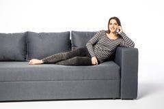 Сотовый телефон счастливой молодой женщины говоря пока лежащ на софе на белизне Стоковые Изображения RF