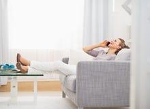 Сотовый телефон счастливой молодой женщины говоря пока сидящ на софе Стоковые Фотографии RF