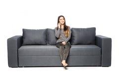 Сотовый телефон счастливой молодой женщины говоря пока сидящ на софе на белизне Стоковое Изображение