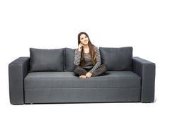 Сотовый телефон счастливой молодой женщины говоря пока сидящ на софе на белизне Стоковая Фотография