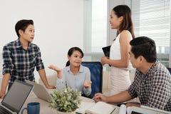 Сотрудники говоря в офисе стоковая фотография