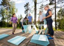 Сотрудники делая пирамиду с деревянными планками на патио Стоковое Фото